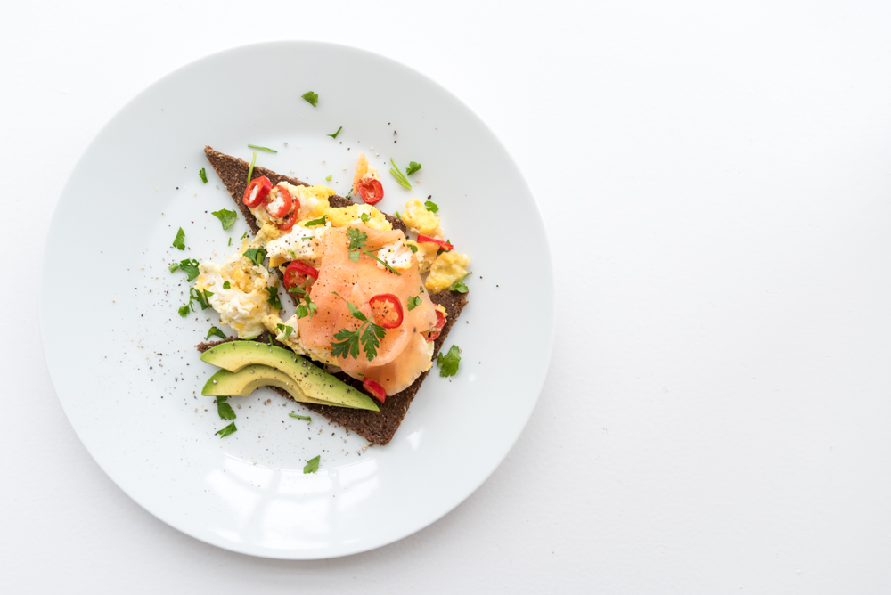 scrambled eggs with smoked salmon and avocado on rye bread on white plate