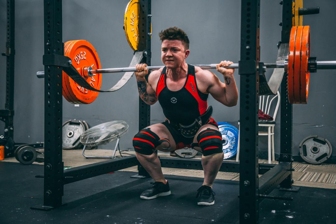 man training legs, barbell squat